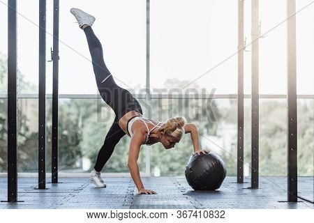 Flexible Fit Woman Doing Functional Training With Medicine Ball In Gym