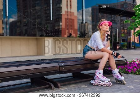 Portrait Of An Emotional Girl On Rollerblades With Pink Cap Visor On Head And Protective Gloves Sitt