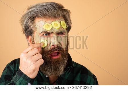 Man Fun Facial. Funny Man With A Clay Mask. Male Bearded Model With Face Cream On The Face. Man Faci
