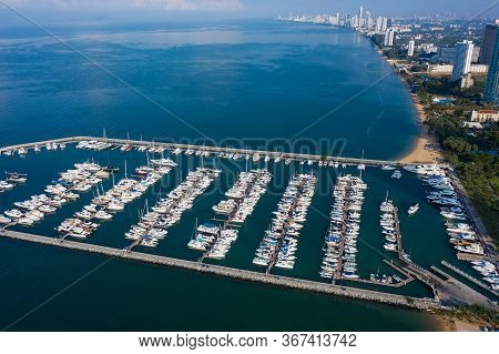 Aerial View Of A White Motor Yacht. Yacht Enters The Bay In The Parking Lot. Many Different Yachts,