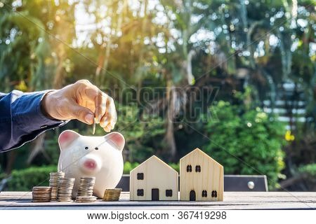 Hand Putting A Coin Into Piggy Bank And Green Nature Background. Planning Savings Money Of Coins To