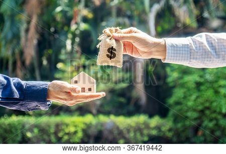 Model House And Money Bag In The Hands Of Investors.save Money For Buying A New Home And Borrowing M