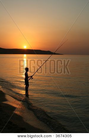 The Silhouette Of One Fisherboy On The Sea.