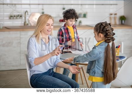 Blonde Female Sitting At Round Table, Spraying Antiseptic On Dark-haired Girl Hands, Boy Standing Be