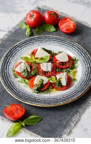 Classic Caprese Salad. Served With Tomatoes, Mozzarella, Arugula, Basil And Pesto.