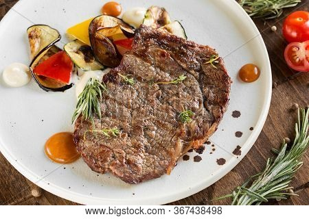 Grilled Beef Steak On A White Plate. Served With A Side Dish Of Vegetables.