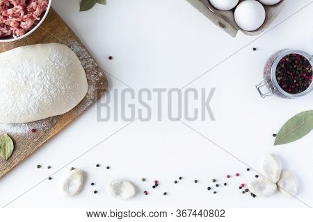 The Dough Lies On The Table, Next To Minced Meat, Eggs, Flour. White Background. Dumplings, Russian