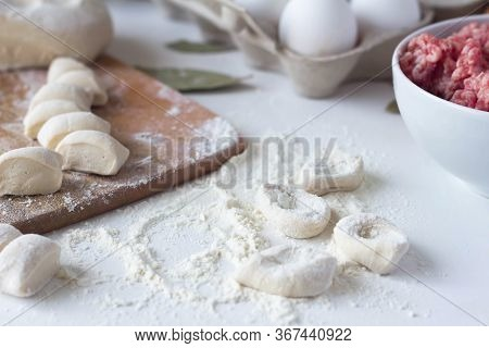 The Dough, Cut Into Pieces, Lies On A Table In Flour. Near The Minced Meat. Dumplings, Russian Cuisi