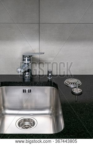 A Close Up Of A Very Clean Kitchen Sink And Faucet And Black Quartz Stone Worktop With Strainer And