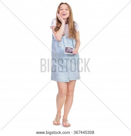 Pregnant Woman In Denim Sundress Standing Looking Smiling, Holding Ultrasound Picture On White Backg