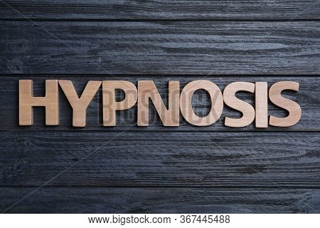 Word Hypnotherapy Made With Wooden Letters On Black Background, Flat Lay