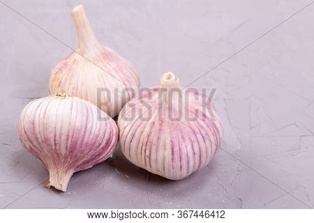 Three Heads Of Garlic Close-up On A Gray Background