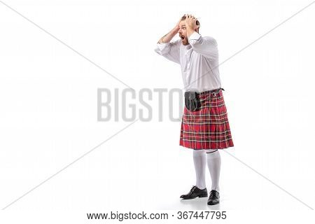 Shocked Scottish Redhead Bearded Man In Red Tartan Kilt Holding Head With Open Mouth On White Backgr