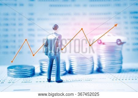 Back Of Miniature Businessman And Blurred Coins, Car And Bankbook With Growing Graph , Blue Color Fi