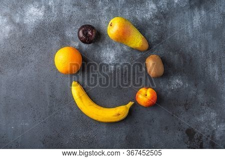 Ingredients For Fruit Salad Lies In The Shape Of A Circle On A Dark Wooden Surface. Top View. Copy S