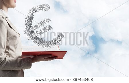 Businesswoman With Euro Currency Sign From Letters Above Opened Notebook. Investment And Money Savin