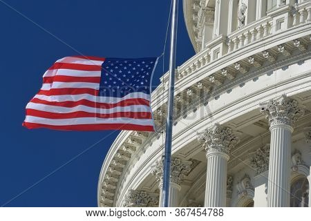 U.S. Capitol Dome  and waving US National flag close-up - Washington D.C. United States of America