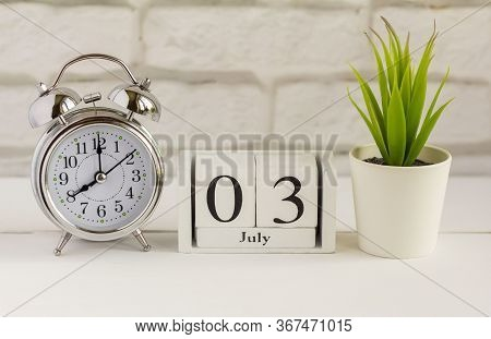 July 3. Wooden Calendar With Date And Table Clock With Bells On The Table Or Shelf. It's July.high S