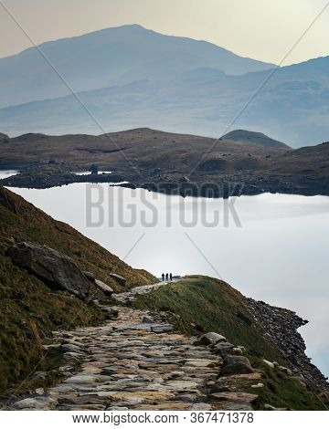 Three Hikers In The Distance On The Paths Of Snowdonia