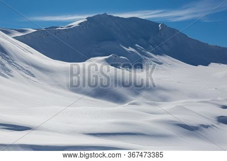 Snowcapped Sandhubel Mountain Near Arosa In Winter Snowscape And Blue Sky