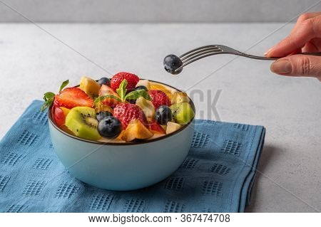 Salad Of Various Fruits. Womans Hand Holds Fork With A Berry. Copy Space For Text