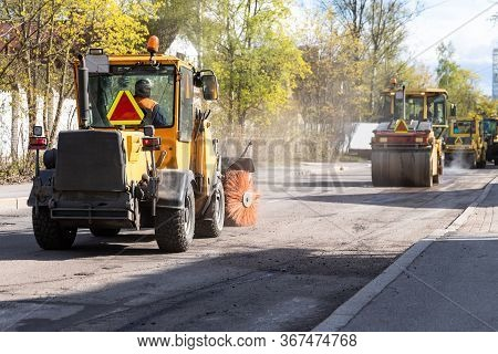 Tractor With Spinning Brush Cleaning Newly Laid Asphalt. Reconstruction And Repair Of A Street Road,