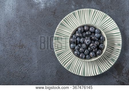 Blueberries Into Bowl On A Plate On A Dark Wooden Background. Top View. Copy Space For Text