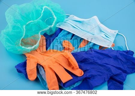 A Pair Of Thin Blue And Orange Medical Latex Gloves And A Protective Mask On A Blue Background. Disp