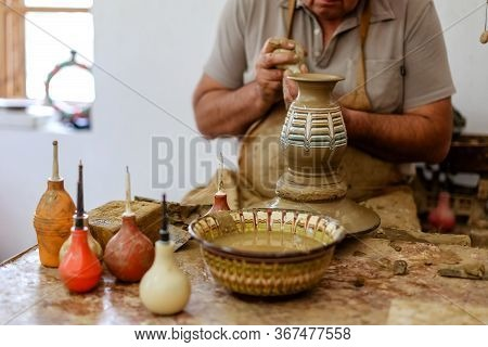 A Potter Makes A Jug With His Hands A Vase Made Of Brown Clay On A Potter's Wheel In A Traditional B