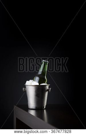 Bottle Of Beer In An Ice Bucket Filled With Ice Cubes Placed On A Bar Counter With Copy Space