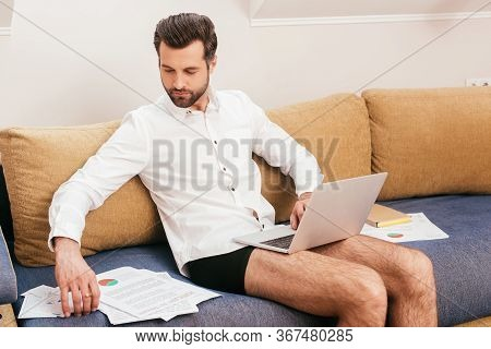 Freelancer In Panties And Shirt Using Laptop And Working With Papers On Sofa At Home