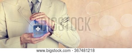 Insurance Concept. Health Insurance. The Insurance Agent Holds A Protective Sphere With The Image Of