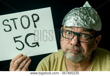 Strange man in a foil hat with a poster Stop 5G. Conspiratorial fake news about coronavirus and mobile communication concept