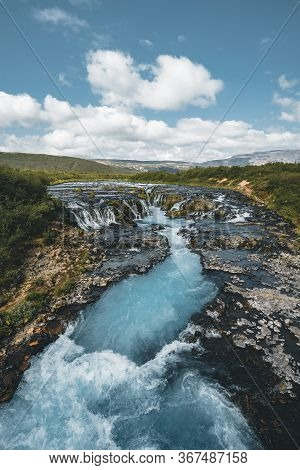 Incredible View Of Bruarfoss Waterfall. The Iceland S Bluest Waterfall. Blue Water Flows Over Stones