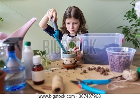 Girl Child Plants Leaf Of Saintpaulia Young Plant In Pot. Uses Spatula, Watering Can, Ground. New Pl
