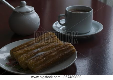 A Cup With Chocolate And Milk And A Plate With Some Traditional Spanish Churros. Spanish Breakfast.