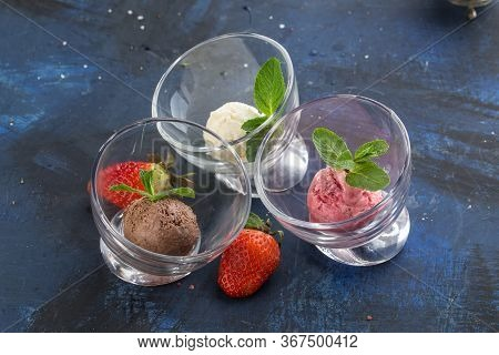 Three Scoops Of Chocolate, Strawberry And Vanilla Ice Cream In Glass Bowl On Blue Background