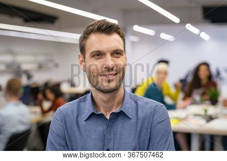 Contemplative mid adult man entrepreneur standing in office with business staff working in background. Portrait of creative business man thinking with optimistic expression, future and vision concept.