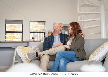 Retired mature couple sitting on couch together. Senior husband with smiling wife sitting on sofa and embracing while looking at each other. Happy old couple in love holding hands.