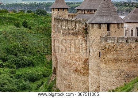 Old Brick Wall Of The Khotyn Fortress Castle In Ukraine On A Background Of Green Trees In Summer. Ho