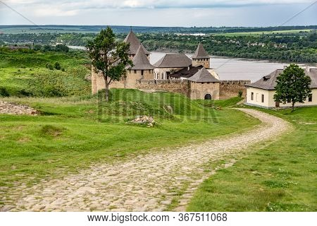 Khotyn Fortress Castle In Ukraine And The Road To It, River On A Background Of Dark Clouds On A Clou