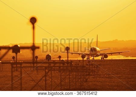 Mid Size Airplane Taking Off On Runway Of Small Airport At Sunset Of Hazy Day.