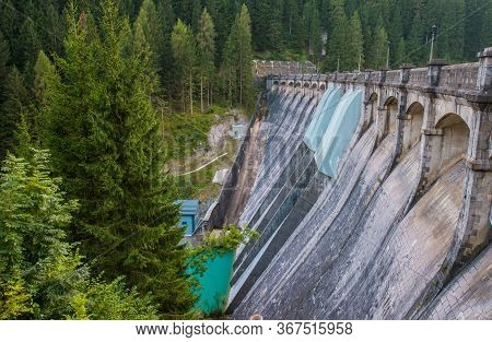 View Of Italian Auronzo Di Cadore Enormous Dam With Turquoise Water Below And Pine Trees Around.