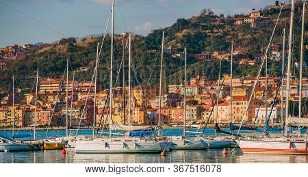 Sailing Boats Docked In Port Of Italian Region Of Liguria And Buildings Along Hillside In Background