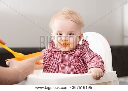 Mom Feeds Baby With Fruit Puree At Home
