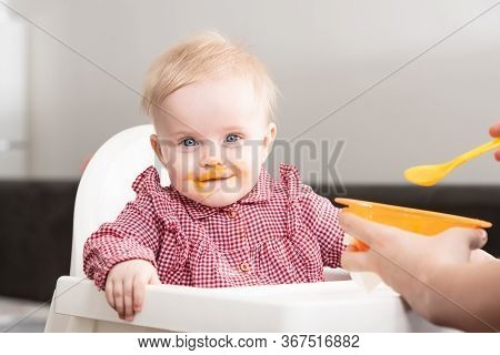 Mother Feeding A Baby In Living Room