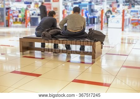 Holiday Shopping Men With Women Concept. Two Unrecognizable Tired Men Are Sitting On A Bench In A Sh