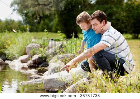 Father and son playing near park lake, looking for animals in the water
