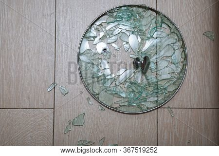 A Close-up Of A Broken Glass Lid Lies On A Stake Of Tile. Shards Of Glass Shine. Soft Focus, Top Vie