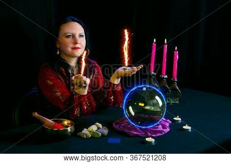 Young Clairvoyant And Fortune Teller With Candles In Hands In A Magic Salon On A Black Background.